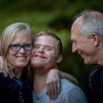Glueckliche Familie - Mutter, Vater und Sohn mit geistiger Behinderung