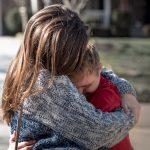 Mädchen umarmt Junge mit geistiger Behinderung